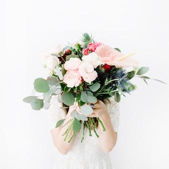 美しい花の花束を持つきれいな女性は、大げさなバラ、青いエリンギウム、アンスリウムの花、白い壁にユーカリの枝を持っています。正面図
