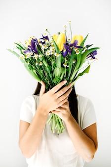 美しい花の花束を持つきれいな女性: 白い壁にチューリップ、カモミール、アイリスの花。フローラル ライフ スタイル構成。