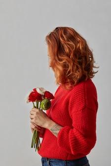 아름다운 폭시 머리를 가진 예쁜 여자가 꽃다발을 들고 있습니다. 봄과 여름 휴가. 아름다움, 패션 개념입니다.