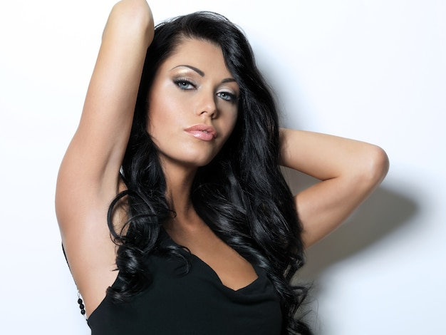 美しさの長い茶色の髪のきれいな女性-スタジオでポーズ