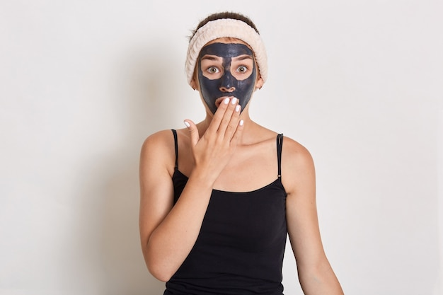 Pretty woman with black clay facial mask, surprised girl with hair band on her head