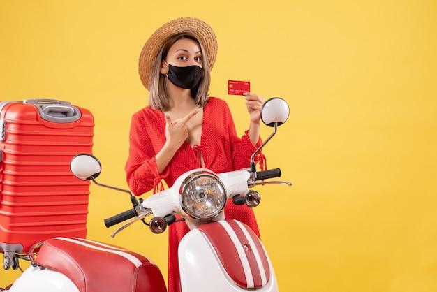 Bella donna con maschera nera in possesso di carta di credito in piedi vicino al motorino