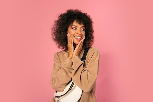 Красивая женщина с черной кожей и стильной африканской прической в спортивном наряде позирует на розовом