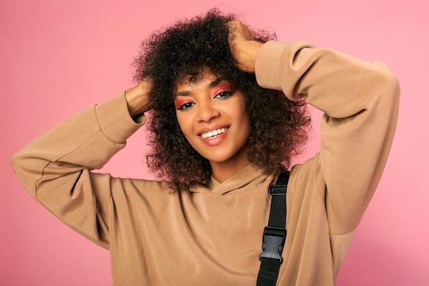 Bella donna con pelle nera e acconciatura africana alla moda in abito sportivo in posa sul rosa