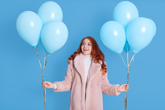 Pretty woman with blue balloons in hands, looking aside with surprised facial expression, wearing faux fur coat, having red wavy hair, celebrating, being in good mood, looks excited.