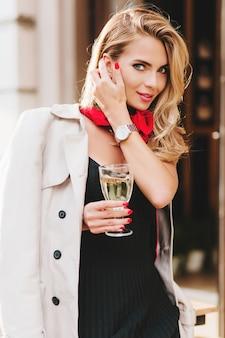 青い大きな目と明るいメイクでお祝いの間に喜んでポーズをとるきれいな女性。通りでシャンパンを飲む光沢のあるブロンドの髪を持つ嬉しい若い女性の外の肖像画。