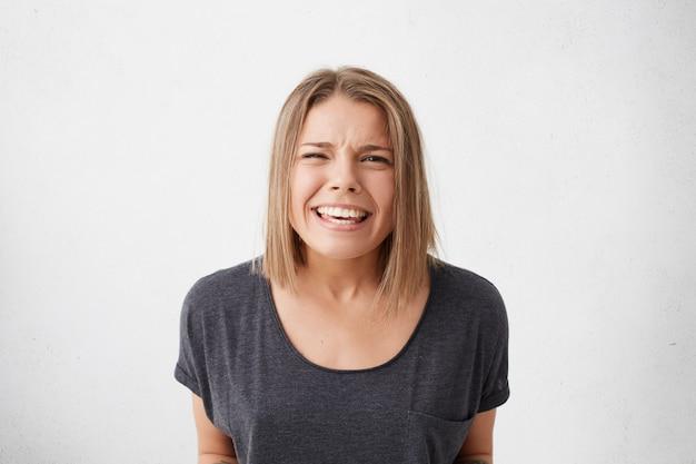 Красивая женщина с прической боб с позитивным выражением лица, широко улыбаясь, с красивыми сияющими глазами, полными счастья.