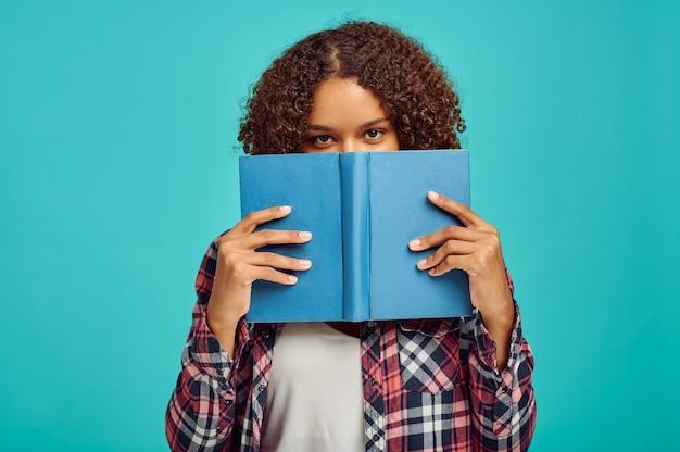 Красивая женщина с книгой, синяя стена, положительные эмоции. выражение лица, лицо женского пола, смотрящее на камеру в студии, эмоциональная концепция, чувства