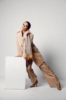 オレンジスタジオと明るいメイクベージュのコートメッシュを持つきれいな女性