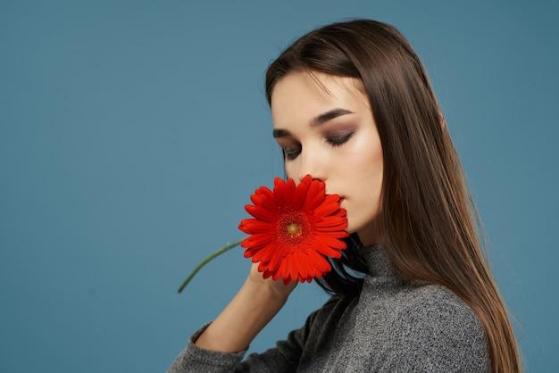 明るいメイクの赤い花のギフトグラマースタジオを持つきれいな女性