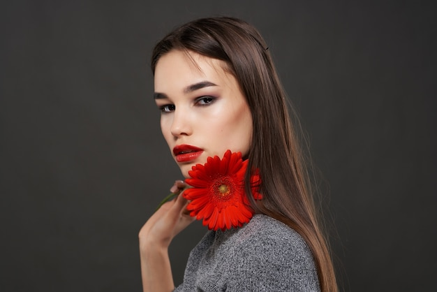 Красивая женщина с ярким макияжем красным цветком возле лица гламур