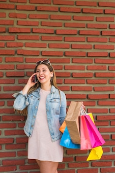 Pretty woman with bright shopping bags talking by phone at brick wall