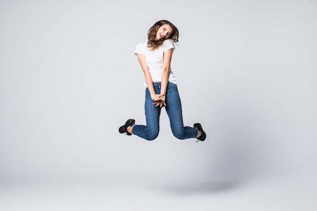 茶色の長い髪と白で隔離のスタジオでジャンプアップ幸せな笑顔の表情のきれいな女性