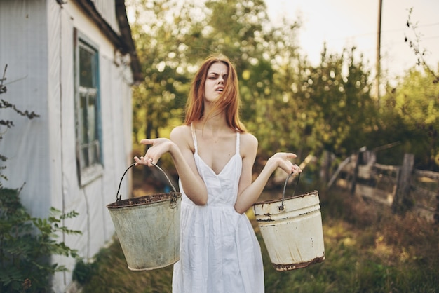Pretty woman with buckets in hand nature lifestyle