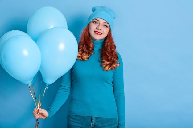 魅力的な笑顔で青い壁にポーズをとって風船の束を持つきれいな女性