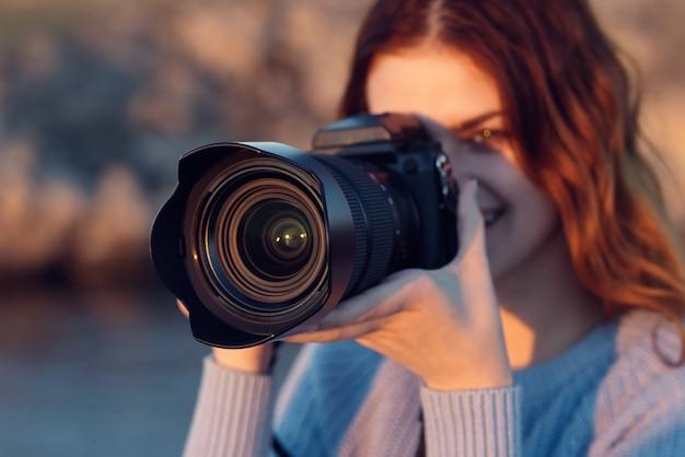 背景の山の川の自然にカメラを持つきれいな女性