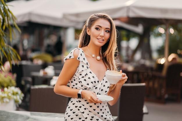 カプチーノのカップと夏のカフェに座って笑っている率直な笑顔を持つきれいな女性