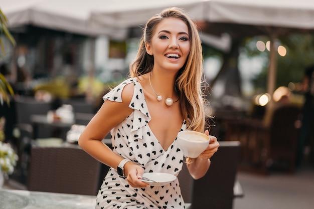 Bella donna con un sorriso candido che ride seduto al caffè estivo con una tazza di cappuccino