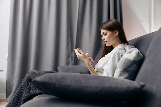 Красивая женщина с мобильным телефоном, сидя на диване