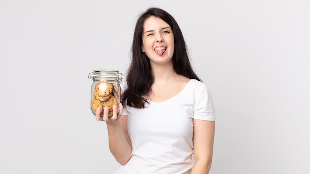 陽気で反抗的な態度、冗談を言って舌を突き出し、クッキーのガラス瓶を持っているきれいな女性