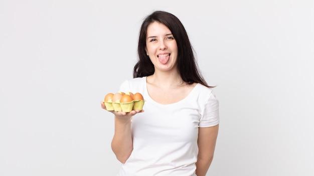 陽気で反抗的な態度、冗談を言って舌を突き出し、卵箱を持っているきれいな女性