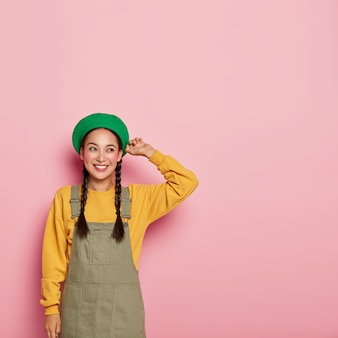 Симпатичная женщина с китайской внешностью, румяна на щеках, стильный берет на голове, толстовка с сарафаном.