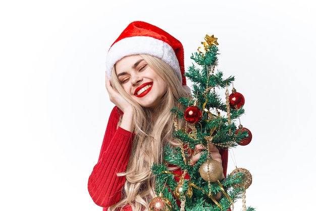 手おもちゃのクリスマスライトの背景にクリスマスツリーを持つきれいな女性。高品質の写真