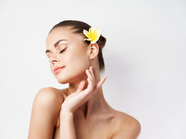 目を閉じて裸の肩を持つきれいな女性が髪の魅力で花を咲かせる