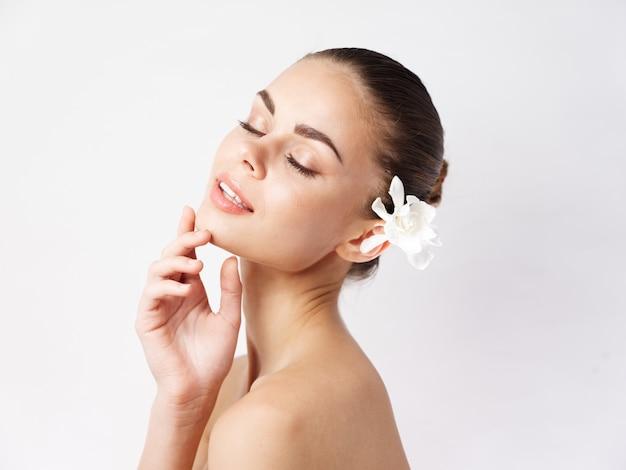 目を閉じて裸の肩の白い花の髪のきれいな女性