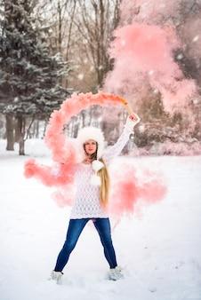 겨울 공원에서 연기 색깔을 가진 예쁜 여자