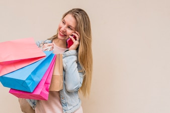 Pretty woman with colourful shopping bags talking by phone