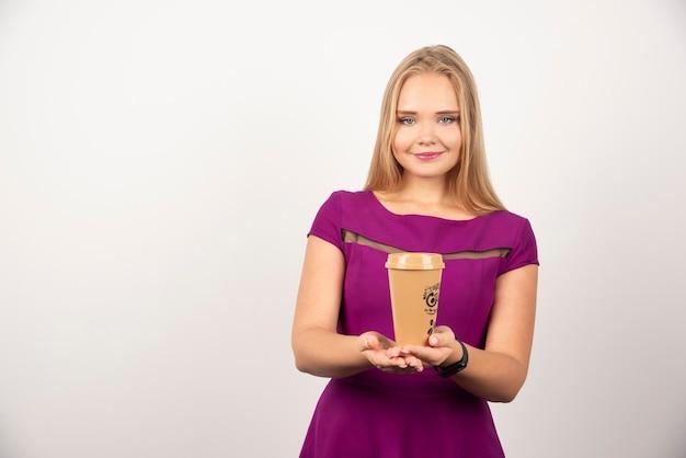 Bella donna con una tazza di caffè in posa contro il bianco.