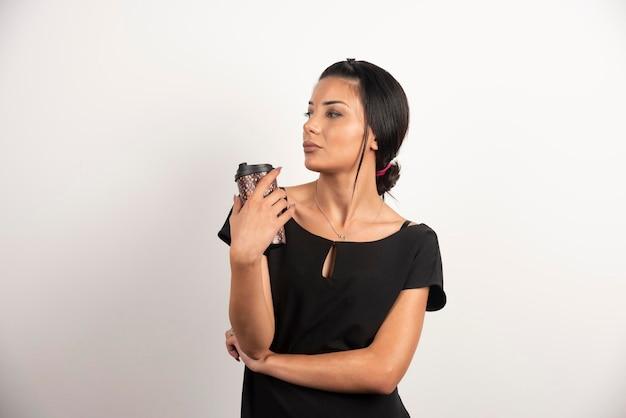 白い壁に立っているコーヒーのカップを持つきれいな女性。