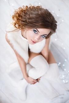 Красивая женщина с кудрями в меховой куртке без рукавов и вязаных чулках сидит на белом деревянном полу