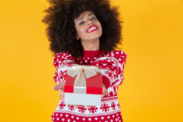 Pretty woman with curly afro american hair, giving a christmas present, yellow background