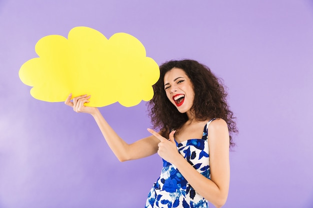 Pretty woman with curly hair in dress smiling and holding blank bubble