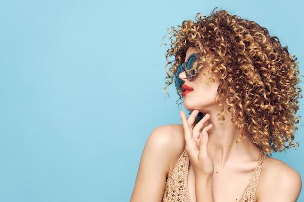 Красивая женщина с вьющимися волосами держит руку возле лица с красными губами в модном стиле крупным планом