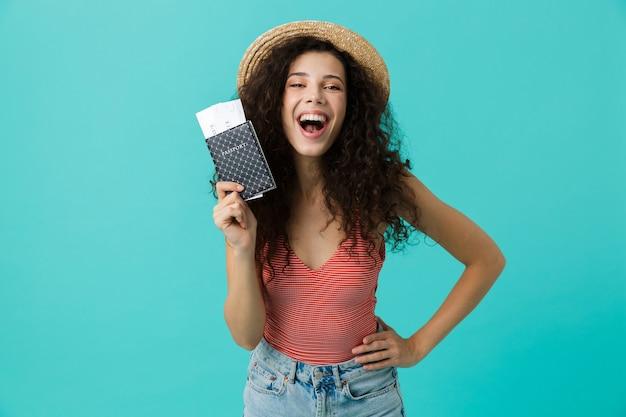 Красивая женщина с вьющимися волосами смеется, держа паспорт и проездные билеты, изолированные на синей стене