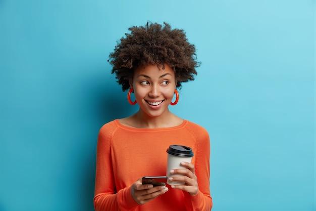 곱슬 머리를 가진 예쁜 여자는 행복하게 소셜 네트워크를 서핑하기 위해 휴대 전화를 사용합니다 테이크 아웃 커피는 파란색 벽 위에 절연 주황색 점퍼를 착용합니다.