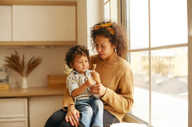 Pretty woman with curly hair sitting on windowsill with adorable baby on her lap, giving him toy or candy, little child looking with interest and curiosity. motherhood, childcare and togetherness