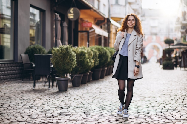 Pretty woman with curly hair walking at a cafe street