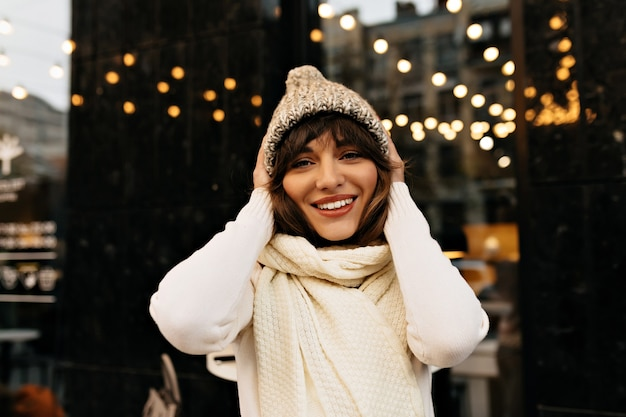 Pretty woman with dark hair having fun outside modern cute female drink preparing for christmas on city background high quality photo