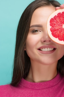 Pretty woman with delicious grapefruit in her arms