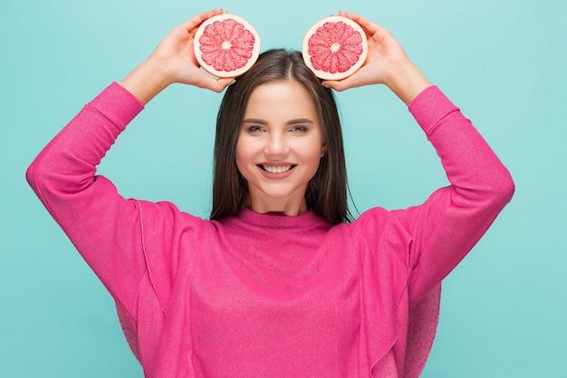 彼女の腕の中でおいしいグレープフルーツを持つきれいな女性。
