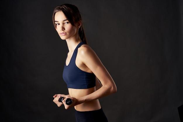운동 운동 고립 된 배경과 손에 아령을 가진 예쁜 여자