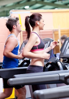 Pretty woman with earphones using a treadmill with her boyfriend in a fitness centre