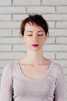 瞑想のように目を閉じて、平和な表情のきれいな女性