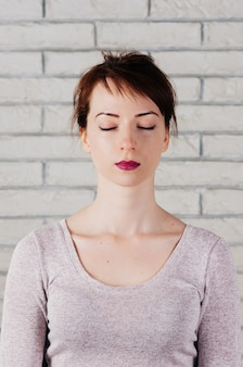 Pretty woman with eyes closed as in meditation, peaceful look