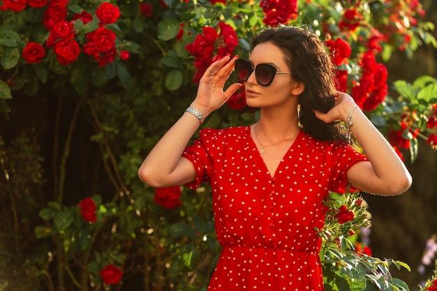 Красивая женщина в модных солнцезащитных очках в красном платье гуляет возле цветов роз на открытом воздухе