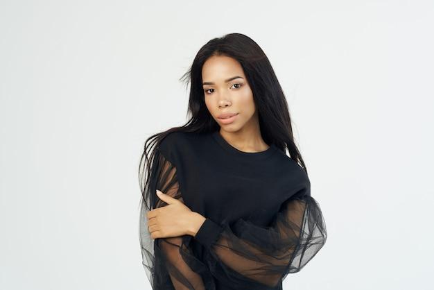 ファッショナブルな髪型のきれいな女性ポーズ黒シャツ明るい背景